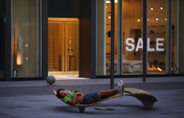 A man sleeps outside a boutique at Taikoo Li Sanlitun North, in Beijing, in this August 24, 2013 file photo. (Photo by Petar Kujundzic/Reuters)