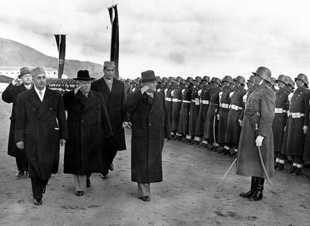 Soviet leader Nikita Khrushchev (black hat), and Marshal Nikolai Bulganin review an Afghan honor guard wearing old German uniforms, on their arrival in Kabul, Afghanistan, on December 15, 1955. At left is the Afghan Prime Minister Sardar Mohammed Daud Khan, and behind, in cap, the foreign minister, Prince Naim. (Photo by AP Photo via The Atlantic)