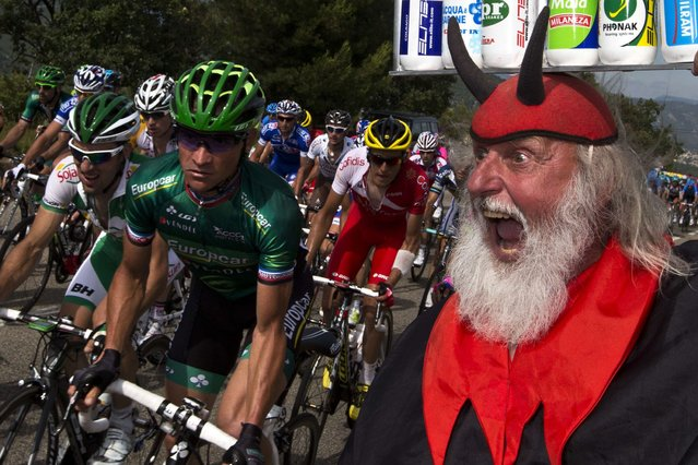 """A disguised spectactor """"El diablo"""" cheers riders during the 228.5 km fifth stage of the 100th edition of the Tour de France cycling race, on July 4, 2013. (Photo by Joel Saget/AFP Photo)"""