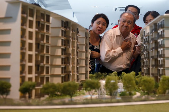 Prospective buyers look at a model of an upcoming suburban private condominium development during its launch in Singapore in this October 25, 2013 file photo.  Singapore is expected to release private home sales figures this week. (Photo by Edgar Su/Reuters)