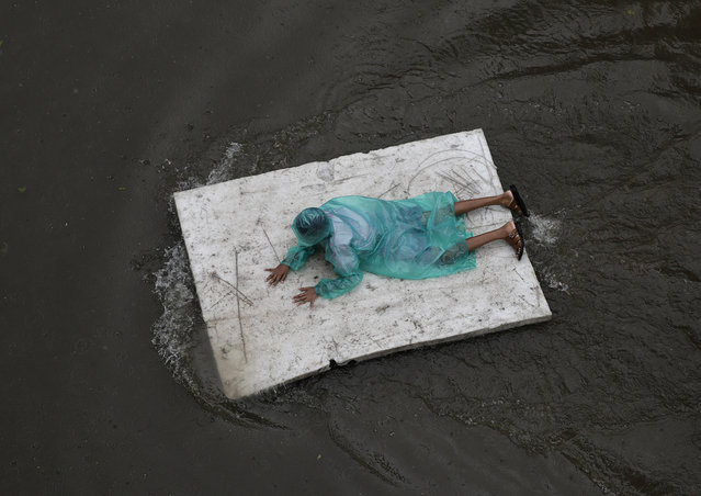 A boy floats on a thermocol sheet on a a waterlogged street in Mumbai, India, Tuesday, July 10, 2018. India's monsoon season runs from June to September. (Photo by Rafiq Maqbool/AP Photo)