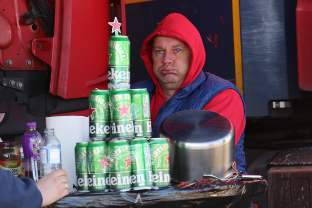 A Polish lorry driver, who has fashioned a makeshift Christmas tree out of empty Heineken cans, waits at a truck stop near Folkestone, Kent on December 25, 2020. Hundreds of travellers are spending Christmas Day as they wait to resume their journey to the Port of Dover and across The Channel now that the borders with France have reopened. (Photo by Gareth Fuller/PA Images via Getty Images)
