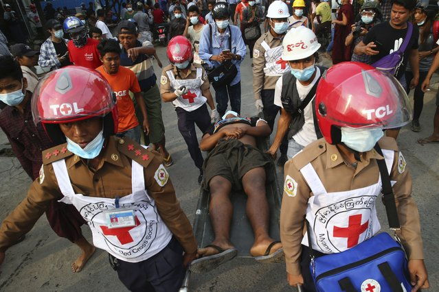 Red Cross workers carry a man on a stretcher in Mandalay, Myanmar on Saturday, February 20, 2021. (Photo by AP Photo/Stringer)