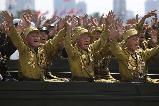 North Korean veterans of the Korean War wave to their leader Kim Jong Un during a mass military parade on Kim Il Sung Square in Pyongyang to mark the 60th anniversary of the Korean War armistice Saturday, July 27, 2013. (Photo by David Guttenfelder/AP Photo)