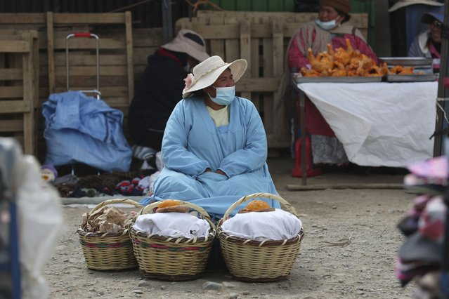 A bread vendor waits for customers in a market in El Alto, Bolivia, Saturday, October 17, 2020. Sunday's presidential election gives Bolivians a chance for a political reset as they struggle with the dramatic costs of the COVID-19 pandemic. (Photo by Martin Mejia/AP Photo)