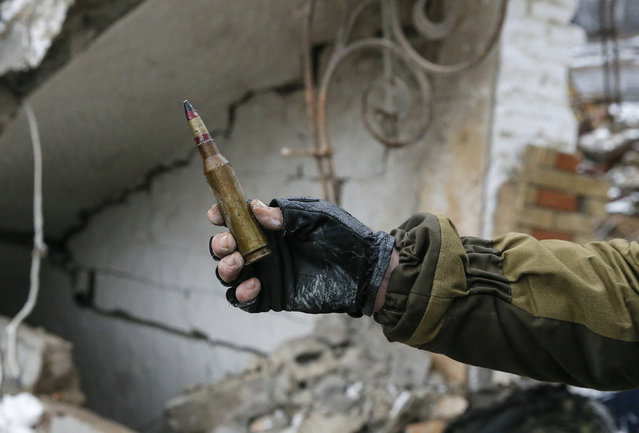 A member of the armed forces of the separatist self-proclaimed Donetsk People's Republic holds up a large-caliber bullet for the camera in Vuhlehirsk, Donetsk region, February 4, 2015. (Photo by Maxim Shemetov/Reuters)