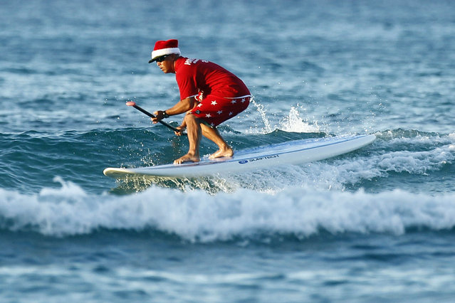 Waikiki Beach surfing instructor John Kepoo wears a Santa hat as he rides the waves at sunrise on Christmas morning in Honolulu, December 25, 2011. Hawaii will enjoy a temperature of 82 degrees (28 Celcius) as U.S. President Barack Obama and his family spend the holidays on Oahu Island. (Photo by Jason Reed/Reuters)