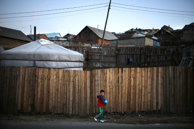 A boy walks along a street next to a ger, a traditional Mongolian tent, in an area known as a ger district in Ulan Bator June 26, 2013. Approximately 60 percent of the population of Ulan Bator live in settlements known as ger districts and in many cases residents have limited access to basic services such as water and sanitation. According to a 2010 National Population Center census, every year between thirty and forty thousand people migrate from the countryside to the capital Ulan Bator. Ger districts in the city have been expanding rapidly in recent years. Mongolia is the world's least densely populated country, with 2.8 million people spread across an area around three times the size of France. (Photo by Carlos Barria/Reuters)