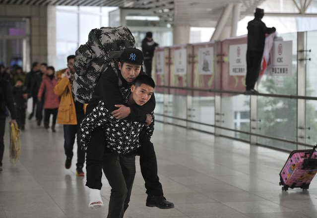 A paramilitary policeman carries a man, who suffers a foot injury, on his back to board their train at a railway station during the travel rush period ahead of the Chinese Lunar New Year in Hefei, Anhui province February 5, 2015. The paramilitary policeman offered to carry the man to his seat after finding out that they were boarding the same train. (Photo by Reuters/Stringer)
