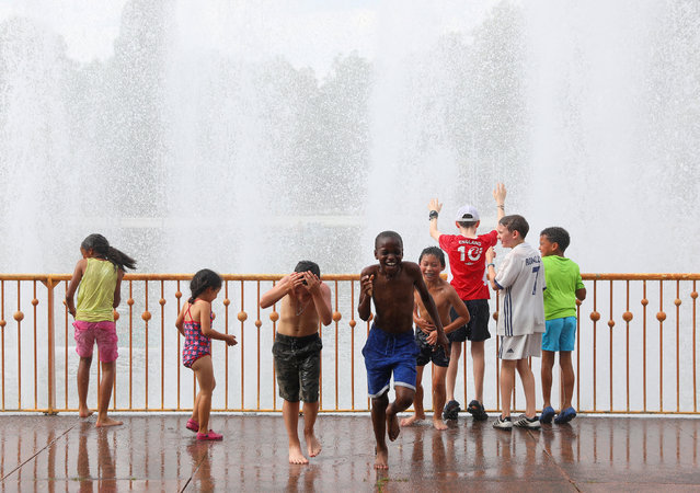 Children play next to a fountain in Battersea Park, London, Britain, July 26, 2018. (Photo by Simon Dawson/Reuters)