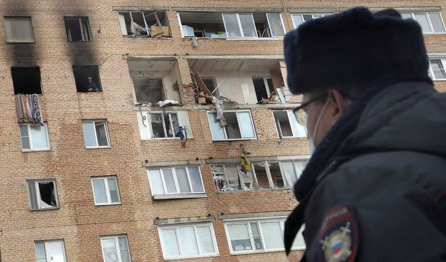 A policeman looks at a nine-storey residential building in the aftermath of an explosion, in Khimki, outskirts of Moscow, Russia, 19 March 2021. A gas explosion at an apartment caused a collapse between the 8th and 9th floor of the complex. A man and a child were found dead. (Photo by Maxim Shipenkov/EPA/EFE)