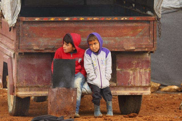 Internally displaced Syrian boys sit on the back of a vehicle at a refugee camp in the Hama countryside, Syria January 1, 2016. (Photo by Ammar Abdullah/Reuters)