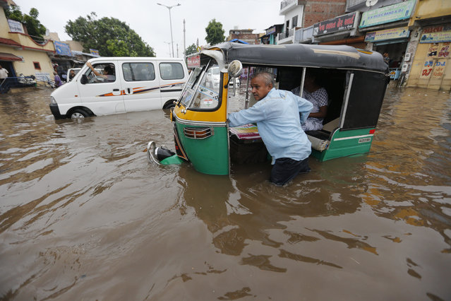 An Indian man pushes an autorickshaw past a flooded street after heavy rainfall in Ahmadabad, India, Friday, August 17, 2018. India receives its annual rainfall from June-October. (Photo by Ajit Solanki/AP Photo)