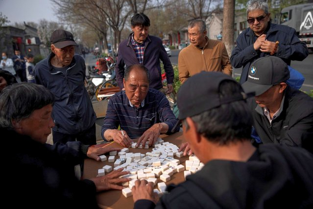 Elderly people play mahjong in Beijing, China, April 6, 2021. (Photo by Thomas Peter/Reuters)