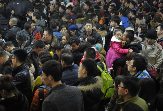 A man kisses a girl at a crowded railway station in Harbin, Heilongjiang province, February 16, 2015. (Photo by Reuters/Stringer)