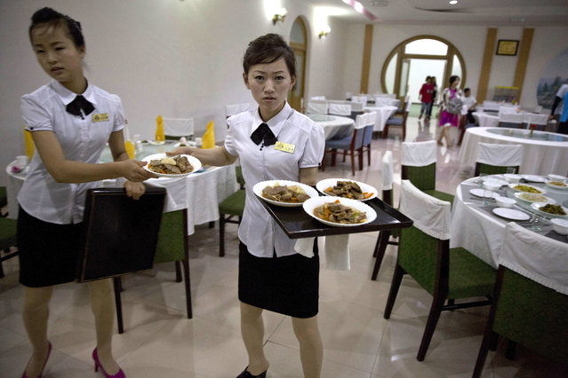 In this Friday, August. 17, 2018, photo, a North Korean waitress prepares to serve dinner to Chinese tourists at the Pegaebong hotel in Samjiyong in North Korea. Chinese businesspeople and tourists are once again flowing over the borders – several large tourist groups were in Samjiyon last week – and South Korean officials are seriously considering ways to help the North improve its roads and railways. (Photo by Ng Han Guan/AP Photo)