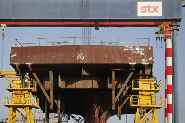 Ship builders work on a section of the Oasis Class 3 cruise ship under construction at the STX Les Chantiers de l'Atlantique shipyard site in Saint-Nazaire, western France, February 17, 2015. (Photo by Stephane Mahe/Reuters)