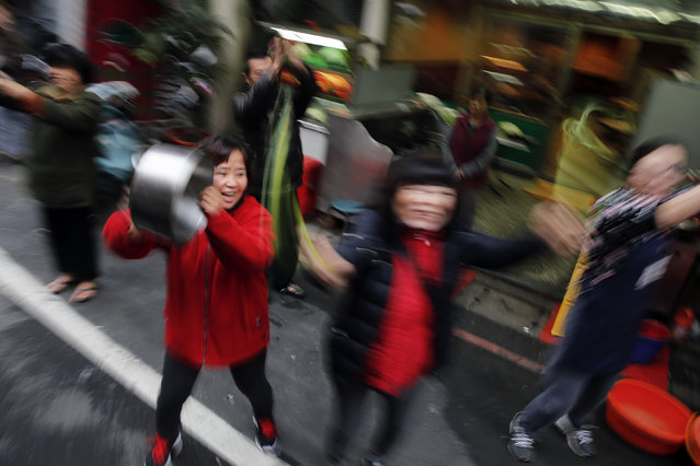 Supporters bang pots and cheer as a motorcade with Taiwan's Democratic Progressive Party (DPP) Chairperson and presidential candidate Tsai Ing-wen (unseen) passes their neighbourhood during a campaign rally in New Taipei City, Taiwan January 13, 2016. (Photo by Damir Sagolj/Reuters)
