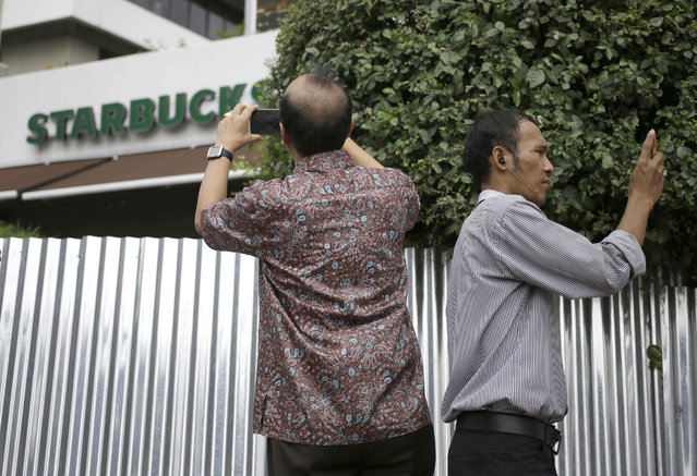 Indonesian men uses their mobile phones to take pictures outside the Starbucks cafe where Thursday's attack occurred in Jakarta, Indonesia, on Friday, January 15, 2016. (Photo by Dita Alangkara/AP Photo)
