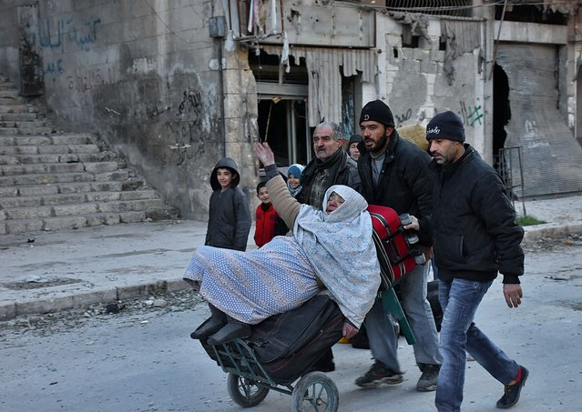 Syrian residents fleeing the violence in the eastern rebel- held parts of Aleppo evacuate from their neighbourhoods through the Bab al- Hadid district after it was seized by the government forces, on December 7, 2016. (Photo by George Ourfalian/AFP Photo)