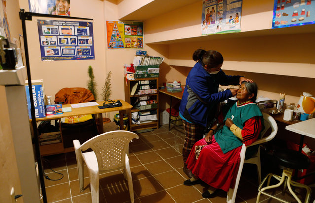 In this February 11, 2105 photo, a doctor checks Aurea Murillo's eyes during a general health check-up after Murillo played a handball game in El Alto, Bolivia. Older people practice sports, play Andean music and recall their younger years through the city sponsored health program that also provides free medical care. (Photo by Juan Karita/AP Photo)