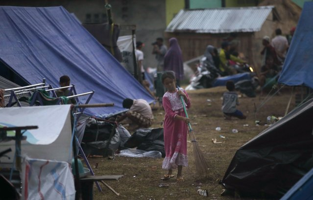 A girl sweeps at a temporary shelter after being displaced by Sunday's earthquake in North Lombok, Indonesia, Wednesday, August 8, 2018. Aid has begun reaching isolated areas of the Indonesian island struggling after an earthquake killed over 100 people as rescuers intensify efforts to find those buried in the rubble. (Photo by Tatan Syuflana/AP Photo)