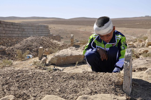 Mohammed Moses grieves by the grave of his father Oktober 7, 2013, who was killed Sunday by a suicide car bomb attack near the Qabak elementary school in the Shiite Turkomen village of Qabak, Iraq. (Photo by Asociated Press)