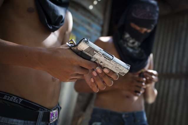 Mara Salvatrucha (MS) gang members with their weapons in Las Victorias district of San Salvador. In March 2012, the two largest gangs in El Salvador – the Mara Salvatrucha (MS) and the Barrio 18 (M18) – agreed on a truce following secret negotiations between gang leaders in prison which were mediated by a bishop and a former rebel leader. It is unclear whether the decision was the idea of the gangs themselves or whether they were encouraged by the government. The murder and kidnapping rate has fallen significantly since the beginning of the truce but it remains unclear how long the truce will hold. (Photo by Adam Hinton)