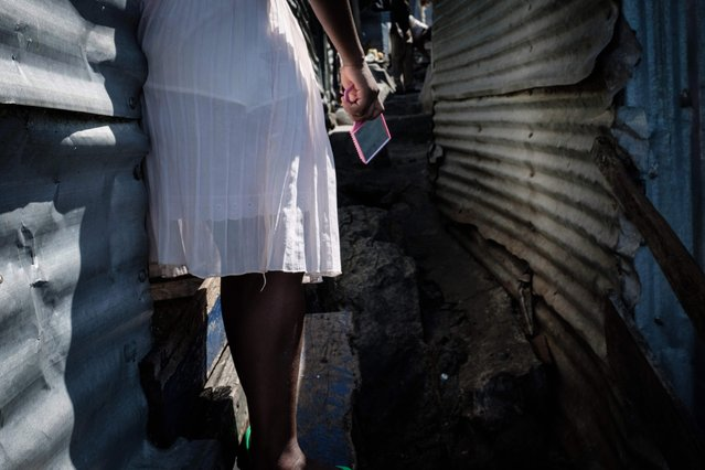 A woman holds a hand mirror on Migingo island on October 5, 2018 which is densely populated by residents fishing mainly for Nile perch in Lake Victoria on the border of Uganda and Kenya. (Photo by Yasuyoshi Chiba/AFP Photo)