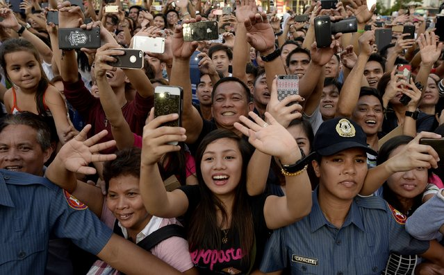 Police (bottom R and L) hold back fans as thousands of people turn out to see Miss Universe Pia Alonzo Wurtzbach as she attends her victory homecoming parade in Manila on January 25, 2016. Wurtzbach was crowned Miss Universe in December in a drama-filled show after the pageant's host, comedian Steve Harvey, misread his cue card and initially announced Miss Colombia as the winner before apologizing and saying Wurtzbach had won. (Photo by Noel Celis/AFP Photo)