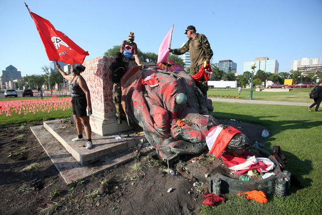 A defaced statue of Queen Victoria lies after being toppled during a rally, following the discovery of the remains of hundreds of children at former indigenous residential schools, outside the provincial legislature on Canada Day in Winnipeg, Manitoba, Canada on July 1, 2021. (Photo by Shannon VanRaes/Reuters)