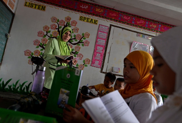 """Zainab Omar, 41, teacher, from Taguig city, teaches her pupils Koranic verses at a religious school in Taguig city, Metro Manila, Philippines October 14, 2016. """"The children are safer now. Parents used to accompany their children to school before Duterte sat as president. Now they let their children go to school by themselves"""", she said. (Photo by Ezra Acayan/Reuters)"""