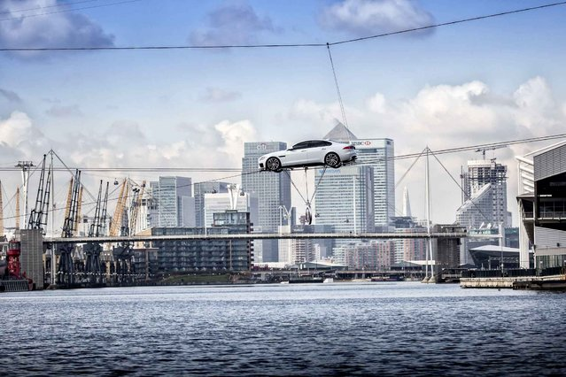 In this photo released on Tuesday, March 24, 2015, the all-new Jaguar XF performs the world's longest high-wire water crossing in the heart of London's business district. Hollywood stunt driver Jim Dowdall drove the all-new XF 240 metres across two 34mm carbon wires which were suspended 18 metres above the water. (Photo by Jaguar via AP Images)