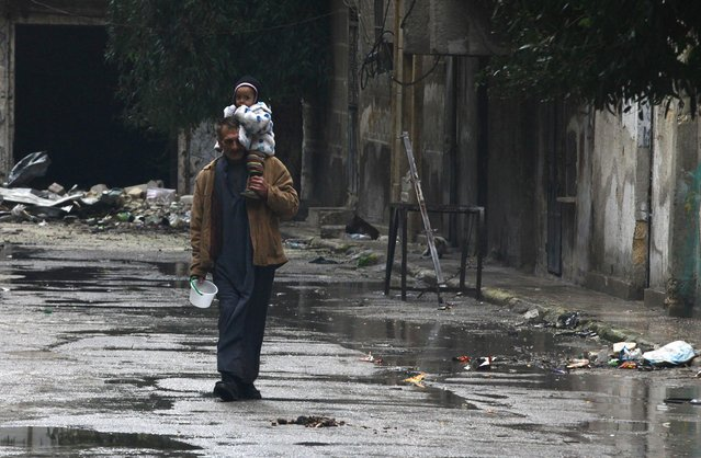 A man carrying a child walks down a street in Old Aleppo January 3, 2015. (Photo by Nour Kelze/Reuters)