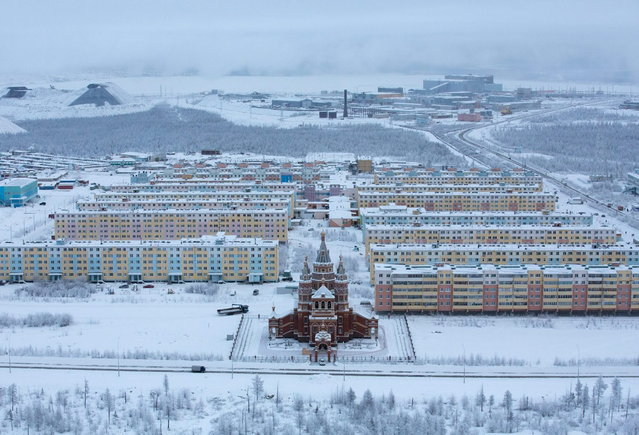 Residential apartment blocks for workers stand beyond a Russian orthodox church near the Udachny diamond mine operated by OAO Alrosa in Udachny, Russia, on Saturday, November 16, 2013. (Photo by Andrey Rudakov/Bloomberg)