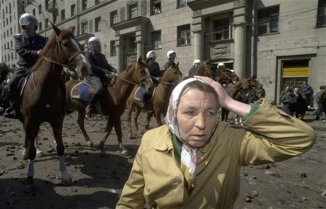 In this file photo taken on Saturday May 1, 1993, an elderly communist woman clutches her head as police on horseback patrol the streets in Moscow. When Alexander Zemlianichenko started working as an AP photographer in Moscow, the Soviet Union was nearing its demise. (Photo by Alexander Zemlianichenko/AP Photo)