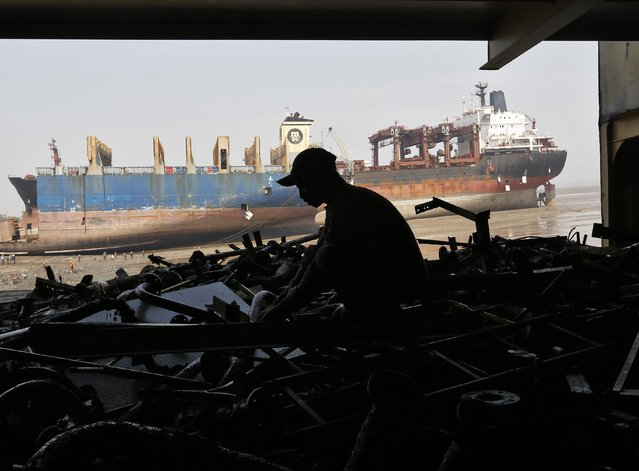 A worker sorts out the engine parts of a decommissioned ship as he dismantles it at the Alang shipyard in the western Indian state of Gujarat, March 27, 2015. (Photo by Amit Dave/Reuters)