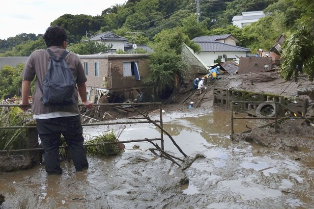 A man watches as rescuers continue a search operation at the site of a mudslide at Izusan in Atami, Shizuoka prefecture, southwest of Tokyo Monday, July 5, 2021. (Photo by Kyodo News via AP Photo)