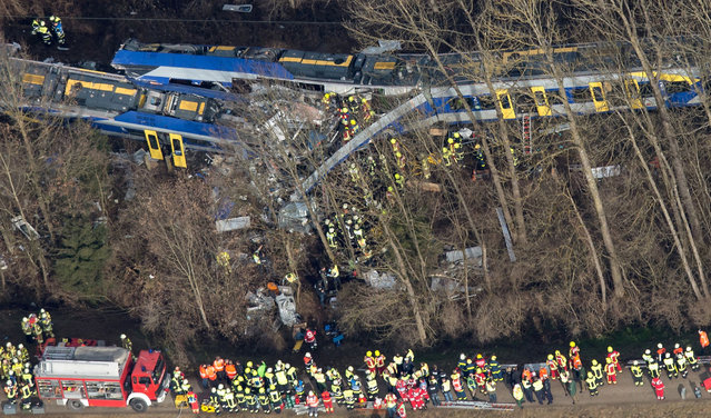 Aerial view shows firefighters and emergency doctors working at the site of a train accident near Bad Aibling, southern Germany, on February 9, 2016. Two Meridian commuter trains operated by Transdev collided head-on near Bad Aibling, around 60 kilometres (40 miles) southeast of Munich, killing at least eight people and injuring around 100, police said. The cause of the accident was not immediately clear. (Photo by Peter Kneffel/AFP Photo/DPA)