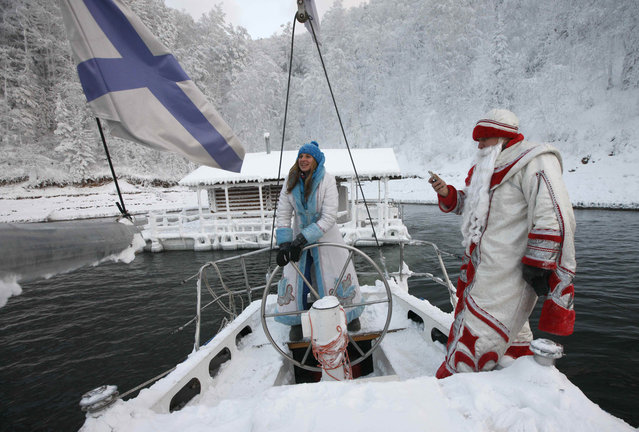 """Members of the """"Skipper"""" yacht club dressed as Father Frost, or Ded Moroz, Russian equivalent of Santa Claus, and his granddaughter Snegurochka (Snow Maiden) sail a yacht along the Yenisei river while marking the end of the sailboat season, with the air temperature at about –17 degrees Celsius, outside Siberian city of Krasnoyarsk, Russia December 8, 2018. (Photo by Ilya Naymushin/Reuters)"""