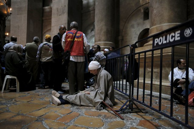 A Christian worshipper sits on the floor in the Church of the Holy Sepulchre in Jerusalem's Old City  during the Greek Orthodox Palm Sunday procession April 5, 2015. (Photo by Ammar Awad/Reuters)