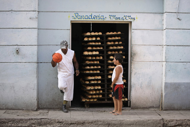 A child looks on as a bakery worker bounces a basketball beside trays of freshly made bread in Havana, Cuba, April 2010. (Photo by Desmond Boylan/Reuters)