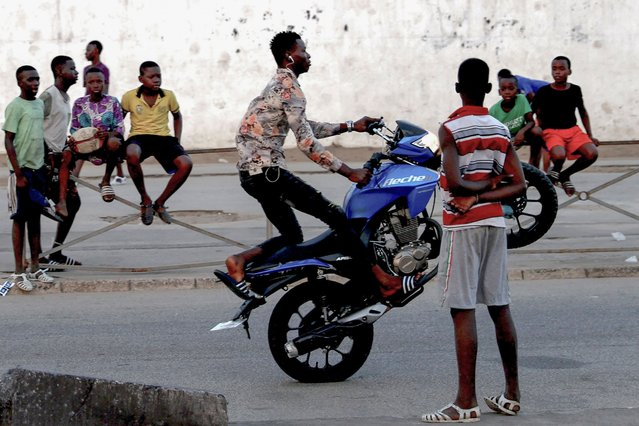 A youth performs on a motorcycle on a street in Abidjan, Ivory Coast on July 28, 2021. (Photo by Mehmet Kaman/Anadolu Agency via Getty Images)