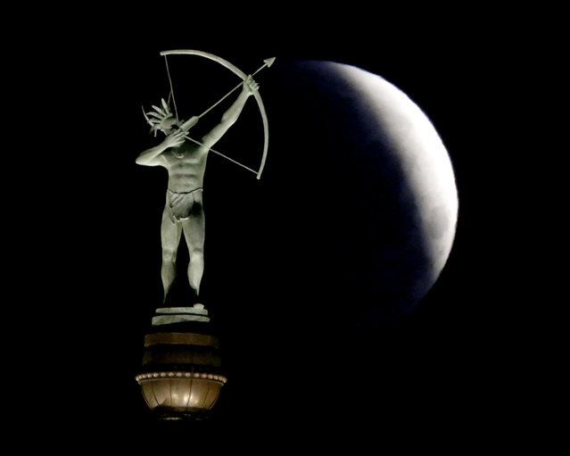 A partially eclipsed full moon sets behind a statue of a Kansa Indian at the Kansas Statehouse, Saturday, April 4, 2015 in Topeka, Kan. The moment when the moon was completely obscured by Earth's shadow lasted several minutes, making it the shortest lunar eclipse of the century. (Photo by Charlie Riedel/AP Photo)