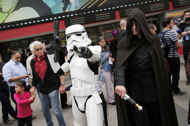 Men dressed as Star Wars characters pose next to people as they queue to attend the steaming of Star Wars Celebration from the Anaheim Convention Center in California, in Paris, France, Thursday, April 16, 2015. (Photo by Christophe Ena/AP Photo)