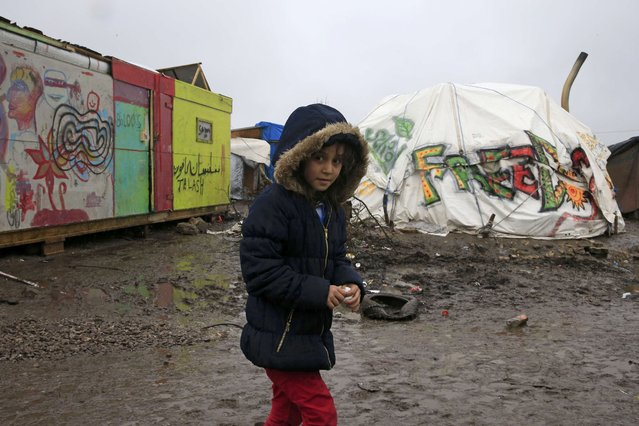 """Aida, a nine-year-old Kurdish girl, walks in the mud in the southern part of a camp for migrants called the """"jungle"""", during a rainy winter day in Calais, northern France, February 22, 2016. French authorities have asked migrants living in tents and makeshift shelters in the southern sector of the """"jungle"""", to leave the area. (Photo by Pascal Rossignol/Reuters)"""