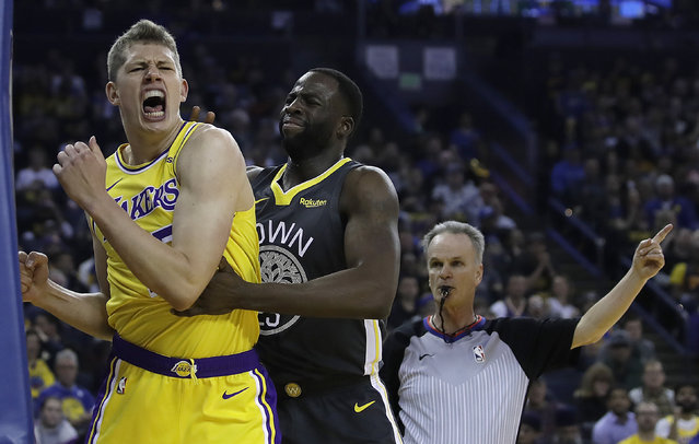 Los Angeles Lakers' Moritz Wagner, left, reacts after a foul is called on Golden State Warriors' Draymond Green, right, in the first half of an NBA basketball game Saturday, February 2, 2019, in Oakland, Calif. (Photo by Ben Margot/AP Photo)