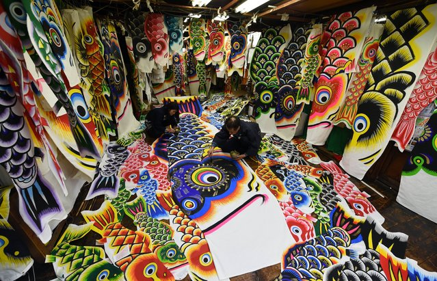 Masaru Hashimoto (R) puts gold paint onto a carp streamer at a factory in Kazo, Saitama prefecture, some 50-kilometre north of Tokyo on April 15, 2015. The 107-year-old Hashimoto Yakichi company produces and sells handmade carp streamers popular during the upcoming Children's Day celebrations where parents wish their boys to grow up as strong as the carp. (Photo by Toshifumi Kitamura/AFP Photo)