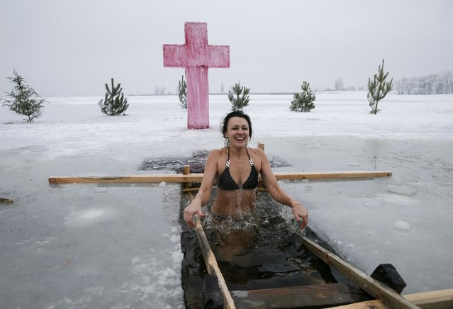 A woman takes a dip in icy waters of the Dnieper river during Orthodox Epiphany celebrations in the town of Vyshgorod, Ukraine January 19, 2017. (Photo by Gleb Garanich/Reuters)