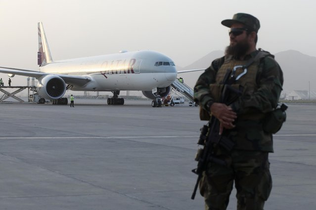 A member of Taliban security forces stands guard in front of a Qatar Airways airplane boarding passengers at the international airport in Kabul, Afghanistan on September 10, 2021. (Photo by WANA (West Asia News Agency) via Reuters)